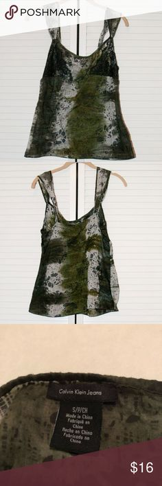 Calvin Klein Jeans Tank Top Size Small Cute Calvin Klein Jeans tank top in a size small. Sheer camo-like print with black lace detail on the bust. Light, sheer material, great for warm spring and summer days! Would be great over a swimsuit top or bralette. Has a side-zip, and the straps have a button adjustment. In very good condition, no flaws that I could see! Comes from a cat-friendly, smoke-free home. Check out my other listings to bundle! Calvin Klein Jeans Tops Tank Tops