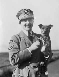 An officer of the Women's Royal Air Force (WRAF) with a dog.