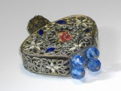 A lovely 1930s Czech. made IRICE perfume bottle consisting of glass under a beautiful pierced metal cage, featuring four blue jeweled feet on the bottom, mini needlepoint decor at the center and on both sides,white enamel flowers and marque shaped blue glass gems. The filigree