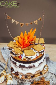 S'moreo Camp Cake! Layers of chocolate cake, 7-minute frosting, double stuffed Oreos, and chocolate ganache. All sandwiched between two graham cracker crusts. Topped with a s'mores campfire, river rock chocolates, and gumpaste flames.
