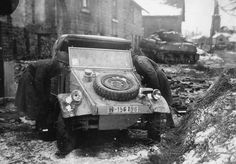 """GIs of the 75th Inf. Div. inspect in the main street at Beffe, 40 Km south of Liège, Belgium, an abandoned VW type 82 """"Kübelwagen"""", belonging to the 2. SS-PzD 'Das Reich'. In the background an Sherman M4A3(76)W from 4th Cavalry Group. 7 January 1945."""