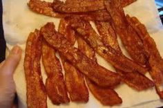 To prevent bacon from shrinking/curling put under cold water before putting it in the pan.