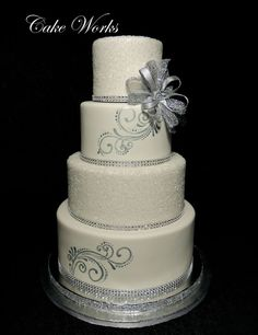 This wedding cake was for a New Year's Eve wedding.  The tiers are all covered in fondant and wrapped with faux rhinestone bling. Two o...