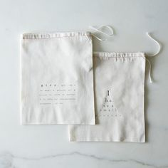 "unbleached cotton drawstring bags printed with the definition of give and an eye chart ""i have a present for you...."" great for wrapping small presents and for reusing over and over. bags are 8 x 9.5"" (20 x 26 cm ) in size."