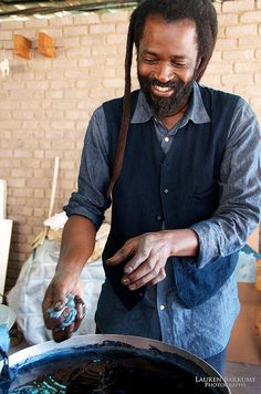 Aboubakar Fofana squeezes out a small cloth to demonstrate indigo dyeing. After each dip, the cloth is squeezed and oxigenated to set the color. Indigo dye and bogolan workshop held with Aboubakar Fofana in Johannesburg, South Africa