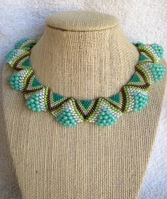 Statement Peyote necklace with an undulating form with crisp colors of aqua, bronze, lime and pearl.
