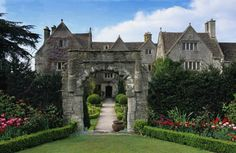 Abbey House, Malmesbury, Wiltshire. The Saxon Arch with path leading through to the Main House. Yew and boxwood topiary.