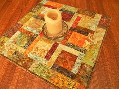 Brilliant autumn leaves are featured in every batik print used for this quilted table topper, in rich shades of red, orange, brown, gold, and green. Its perfect as a decorative accent all by itself or as a table centerpiece with a collection of candles or other fall accessories. The size is approximately 19 square (48 cm). I machine-quilted an all-over meander in gold thread. On the back I used another leaf batik print in soft shades of gold and cream. The binding is doubled for durability…