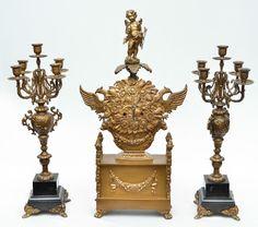"""Lindíssima garniture em bronze europeu, dourado, composta por um grande relógio ladeado por figuras de dragões e encimado por escultura representando """"Anjo"""" e dois lindos candelabros para 5 velas cada com base em mármore negro. Candelabros med. 50cm de altura. 20cm de diametro. Cada. Med.: 59 cm e 49 cm, respectivamente."""