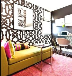 Baroque black and white bold wallpaper in living room with mustard colour couch and bright coloured accents and rug. Feature wall creates a focus point in the room.