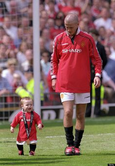 Beckham and his one-year-old son Brooklyn during Manchester United's 2000 title celebrations
