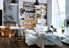 Modernes Schlafzimmer mit einem großen weißen Bett im Vordergrund. Im Hintergrund ist eine geflieste Wand zu sehen, an dem Holzregale mit Kästen stehen.