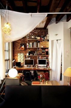 in home Work Space for more than one person. Shelves, lamps, uke, brick wall, exposed beam ceiling
