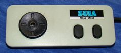 Sega SJ-150 :-: Copying its design from the controller used on the Nintendo Famicom, this game pad was released as the default controller packaged with the Sega SG-1000 II. While the controller replaced the SJ-200 as the standard for Sega consoles, the SJ-150 came with a stick that could be screwed into the D-Pad to turn it into a similar controller. The controllers was not known for its ergonomic design, with the cable coming out to the side rather than the top.
