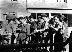 U.S. infantrymen of the 1st Infantry Division, French Resistance fighters and French Colonial African sharpshooters who escaped from a German POW camp in La Ferté-Macé meet up and examine each other's weapons following the liberation of Couterne from German occupation. Couterne, Orne, Lower Normandy, France. 14 August 1944.