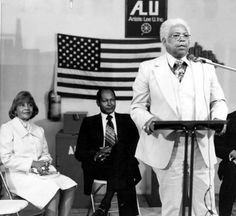 Reverend Hillery T. Broadous addresses the Pacoima community in a meeting which included Mayor Tom Bradley and Mrs. Ethel Bradley, 1977. San Fernando Valley History Digital Library.
