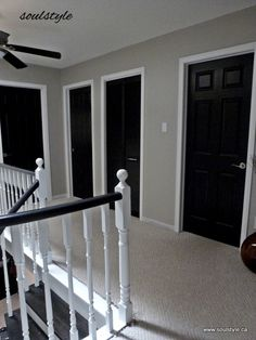 """Black Interior Doors, white trim. Two coats SW all surface lacquer in """"caviar"""" using 1-12/"""" angled brush for panel details, small foam roller on rest for smooth finish. SW """"oxford white"""" for trim. SW """"revere pewter"""" walls."""