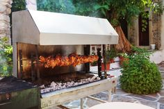 On a sprawling stone floor patio, we see a large open pit grill with rotisserie next to an old fashioned grill.