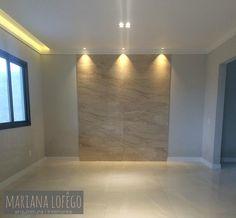 Sala de Estar com detalhe na parede em porcelanato!! O uso da iluminação deu um up na decoração.  E uso de cortineiro iluminado!!