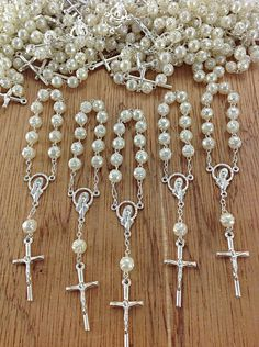 Mini Rosary Baptism Favors 25 pcs Pearl and Silver  Elegant mini-rosary baptism favors. With attention to details and unmistakable craftsmanship, these mini rosaries come with round beads in the shape of a rose, this rosary comes in pearl color beads and silver plated chain and cross. Each measuring approximately 4 1/2 INCHES in length. When selecting a color please keep in mind the following; the 1st color listed is the bead color, the 2nd color listed is the metal finish on the chain and…