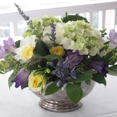 purple and white centerpiece in silver bowl