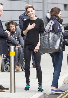 She was wearing her third outfit of the day - a black woven jumper, black jeans and traine...