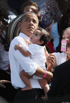 Obama with a baby, who clearly has much better things to see, lol