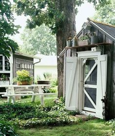 Garden shed w/screen door, love the watering cans above shed!