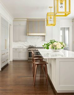 The Urban Electric Company's Cosy #pendants look amazing in this gorgeous #white #kitchen. #kitchenlighting #pendant #interiordesign #interiordesignideas #interiordesigninspiration #homedecor #homedecorideas #homedecorinspiration #whitekitchen #countertops #cabinets #counterstools #whitecountertops