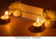 still life candle with flower and note pray for the world  background,candle flame at night. - stock photo