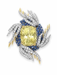 "A DIAMOND, SAPPHIRE AND YELLOW SAPPHIRE ""WINGS"" BROOCH, BY JEAN SCHLUMBERGER, TIFFANY & CO. Set with a cushion-cut yellow sapphire, weighing approximately 35.99 carats, within a circular-cut sapphire surround, extending four circular-cut diamond and sculpted 18k gold wings, mounted in 18k gold and platinum Signed Schlumberger Studios for Jean Schlumberger, Tiffany & Co."