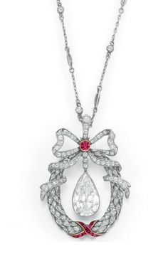 A BELLE EPOQUE DIAMOND AND RUBY PENDANT NECKLACE   Suspending a pear-shaped diamond, weighing approximately 3.76 carats, within a single-cut diamond foliate wreath, decorated with calibré-cut ruby ribbon detail, topped with a single-cut diamond bow, centering upon a collet-set ruby, from the fine link platinum neckchain, spaced by collet-set diamonds, mounted in platinum and gold, circa 1910