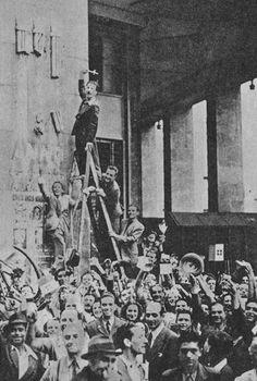 Manifestants milanais détruisant les insignes du fascisme italien (les faisceaux) suite à l'annonce de la destitution de Mussolini