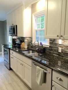 My beautiful galley-style kitchen renovation with Allen Roth Shimmering Lights glass backsplash (from Lowes), white cabinets, and butterfly black granite countertops.