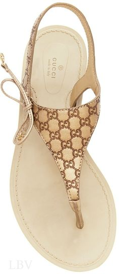 1902bc3ef05360 Gucci Gold Katina Leather Thong Sandals Soft leather sandals defined by a  logo-embossed upper