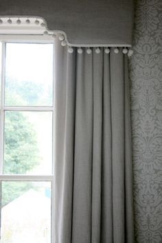 Grey pompom trimmed cornice box with matching drapes.