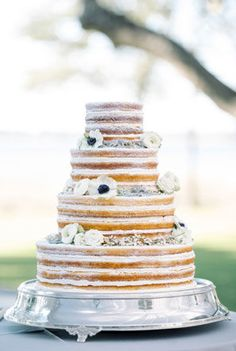 large naked wedding cake on silver stand decorated with white anemones