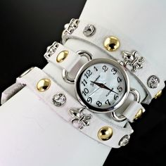 NEW! GENEVA WRAP FLEUR DE LIS  WATCH, THIS IS THE NEWEST MOST WANTED WATCH!! HAS STAINLESS STEEL BACK, JAPAN MOVEMENT AND WATER RESISTANT. NICE!! COLOR IS WHITE WITH SILVER FLEUR DE LIS AND RHINESTONES AND  GOLD STUDS.
