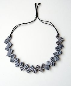 original origami paper necklace with black & white zebra stripes. This paper necklace is handcrafted with a zebra striped paper with the origami technique.  Its length is adjustable, you can adapt it to your liking and is very light to wear. I used finishing products to protect it: withstands water but is NOT waterproof. The black cord is super soft and easy to wear against the neck. It's a first quality cord whose characteristics are the smoothness and brightness of the colors. €26.00