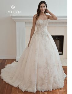 Beautiful lace and tulle ball gown with pleated skirt. The gown is embellished with champagne/silver lace appliques on top of overlace and tulle. Slight illusion sweetheart satin neckline adorned by soft ivory, champagne and silver beadings.  The pleated overlace and tulle skirt is enhansed by the scallop lace around hemline
