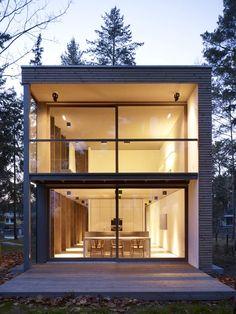 Die Scheidt Kasprusch Architekten verwirklichten das 'Minimum House' in Mellensee bei Berlin. Das Haus dient als Prototyp für ein serielles Ferien- und Wohnhaus. Durch die Verwendung von Glasfronten an drei Seiten des Gebäudes wirkt die Fassade leicht und aufgeschlossen.