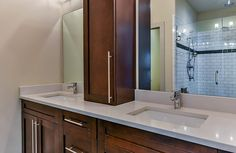 The master bathroom features a double vanity with rectangular sinks, quartz countertop, Grohe plumbing fixtures and modern style hardware. The custom linen tower between the sinks hides additional electrical outlets to charge razors, toothbrushes, etc. You can see the walk in shower with subway tile and glass accent strip in the mirror.