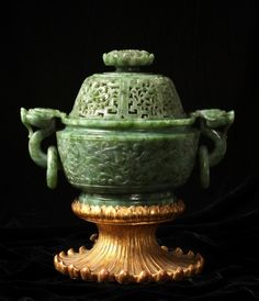 A Chinese spinach green jade potpourri (Lu) and pierced cover, the base with floral designs in relief and having a pair of dragon handles with loose rings; the domed cover pierced with floral traceries below a lotus blossom finial, Qianlong (1736-1795) height: 6 1/2 in. (16.5 cm) SOLD FOR $115,000 (March 2013)