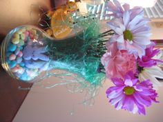 Jelly beans in the bottom, rabbit peeps and Easter grass.  A cone shaped plastic container holds the flowers inside the vase.