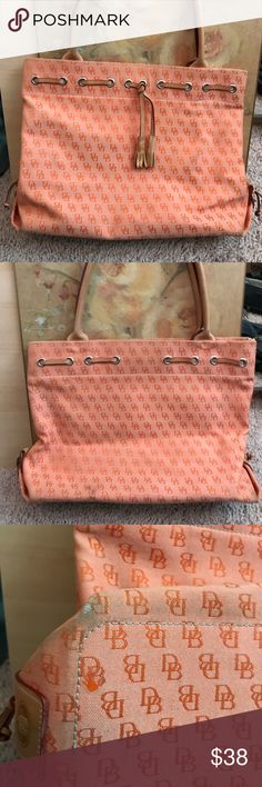 """Dooney & Bourke orange colored larger bag Cute orange D&B bag with leather handles (9 of 10 handle condition) bottom corners have some wear and small spot on back of bag near bottom . Inside is clean has 4 pockets a couple of light pen marks inside add seen in pic. 15"""" wide x 11"""" high x 5"""" wide. Add 9.5"""" with strap. Dooney & Bourke Bags Shoulder Bags"""