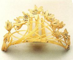 Lalique introduced horn into the jewelry repertoire. In this tiara, c. 1902, the iridescent horn has different hues, lighter in the center, darker on the sides. The flowers have diamond centers. A gold hinge attaches the tiara to a three-pronged tortoiseshell comb.