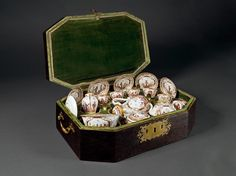 A Meissen Chinoiserie Travelling Tea- and Coffee-Service in the Original Case (1723, Germany). Hard paste porcelain decorated in gold and enamel colours, velvet-lined leather case. The service consists of: The original case, six cups with saucers, one teapot with K.P.M. and swords mark, one bowl, one coffeepot, one tea caddy, one suger box with K.P.F. mark, six Augsburg silver gilded spoons