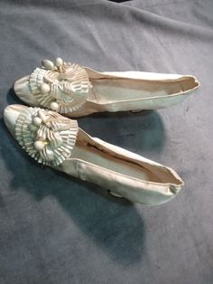 Pair of wedding shoes, 1890. Satin cream rosette flowers and wooden orange on uppers, lined kid