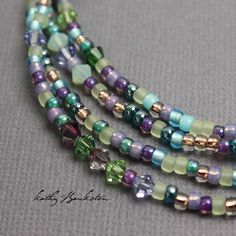 A little sparkly twist on one of my best selling seed bead necklaces A Multicolor blue purple, gold and teal glass seed bead necklace with Swarovski crystals mixed in. All the colors of a summer garde