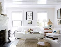 A vintage sofa is covered in easy-to-wash white canvas, and jute rug covers the floor for a fuss-­free and affordable floor covering. A marlin pillow accents the chair. You may find a similar pillow at http://www.seasideinspired.com/4330-marlin-pillow.htm